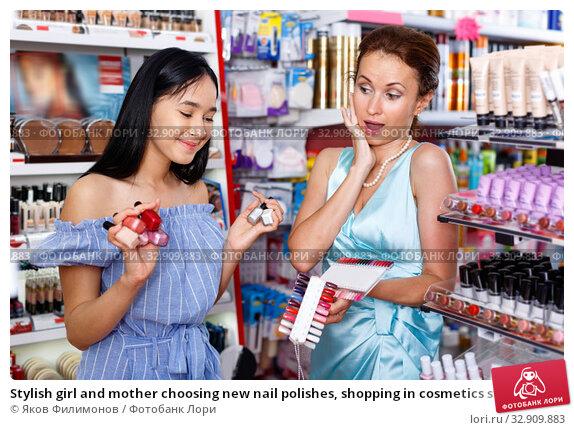 Stylish girl and mother choosing new nail polishes, shopping in cosmetics store. Стоковое фото, фотограф Яков Филимонов / Фотобанк Лори