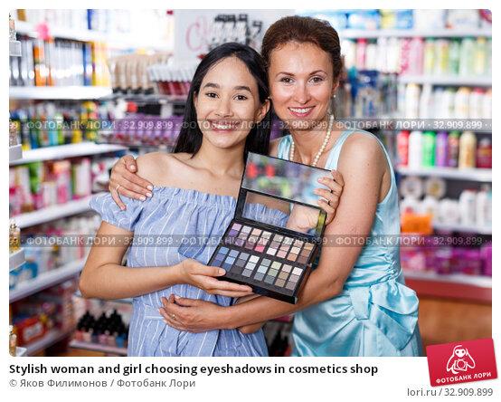 Stylish woman and girl choosing eyeshadows in cosmetics shop. Стоковое фото, фотограф Яков Филимонов / Фотобанк Лори