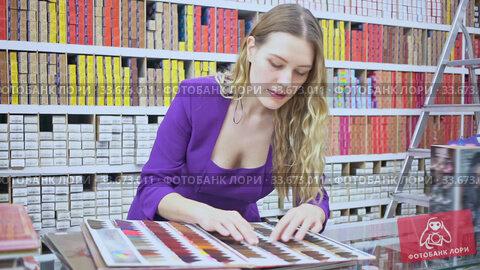 Купить «Stylish young woman choosing color of hair dye from palette in shop», видеоролик № 33673011, снято 12 июля 2020 г. (c) Яков Филимонов / Фотобанк Лори