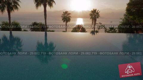 Купить «Swimming pool on resort with sea and mountains view, scene at sunset», видеоролик № 29082719, снято 19 сентября 2018 г. (c) Данил Руденко / Фотобанк Лори
