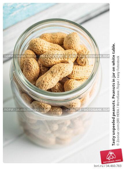 Tasty unpeeled peanuts. Peanuts in jar on white table. Стоковое фото, фотограф Zoonar.com/JIRI HERA / easy Fotostock / Фотобанк Лори
