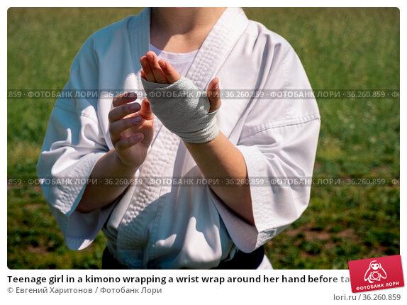 Teenage girl in a kimono wrapping a wrist wrap around her hand before taking karate outdoors. Стоковое фото, фотограф Евгений Харитонов / Фотобанк Лори
