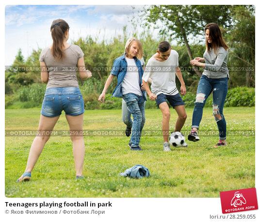 Купить «Teenagers playing football in park», фото № 28259055, снято 21 марта 2019 г. (c) Яков Филимонов / Фотобанк Лори
