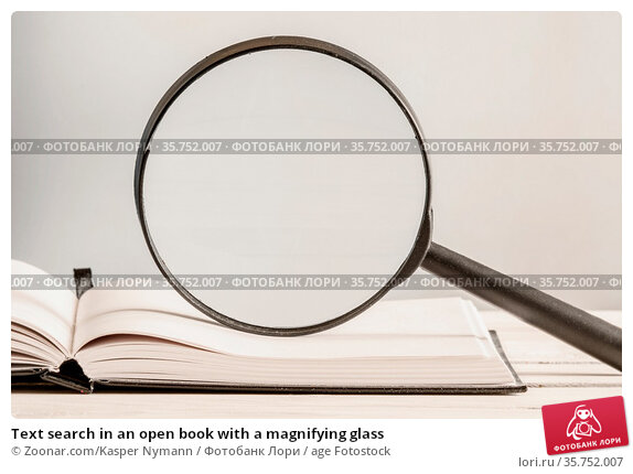Text search in an open book with a magnifying glass. Стоковое фото, фотограф Zoonar.com/Kasper Nymann / age Fotostock / Фотобанк Лори