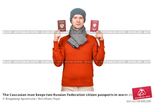 The Caucasian man keeps two Russian Federation citizen passports in warm clothes on a white background. Стоковое фото, фотограф Владимир Арсентьев / Фотобанк Лори