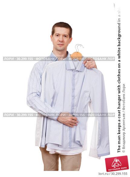 Купить «The man keeps a coat hanger with clothes on a white background in a shirt», фото № 30299155, снято 7 марта 2019 г. (c) Владимир Арсентьев / Фотобанк Лори