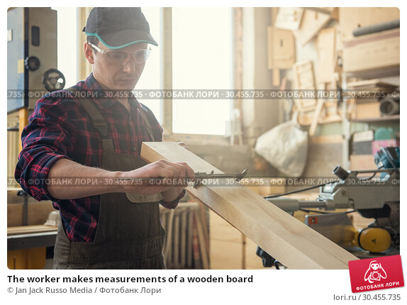 The worker makes measurements of a wooden board. Стоковое фото, фотограф Jan Jack Russo Media / Фотобанк Лори