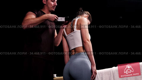 Therapy in dark studio - therapist putting on black stretching tape on the neck of his woman client. Стоковое видео, видеограф Константин Шишкин / Фотобанк Лори