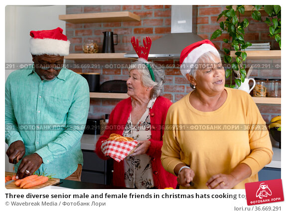 Three diverse senior male and female friends in christmas hats cooking together in kitchen. Стоковое фото, агентство Wavebreak Media / Фотобанк Лори