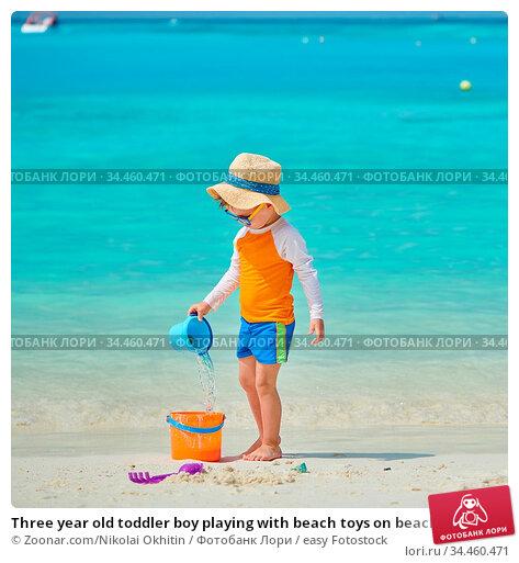 Three year old toddler boy playing with beach toys on beach. Summer... Стоковое фото, фотограф Zoonar.com/Nikolai Okhitin / easy Fotostock / Фотобанк Лори