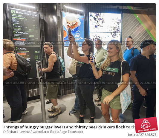 Купить «Throngs of hungry burger lovers and thirsty beer drinkers flock to the Shake Shack in Penn Station in New York on Monday, August 14, 2017 for the happy...», фото № 27326575, снято 14 августа 2017 г. (c) age Fotostock / Фотобанк Лори