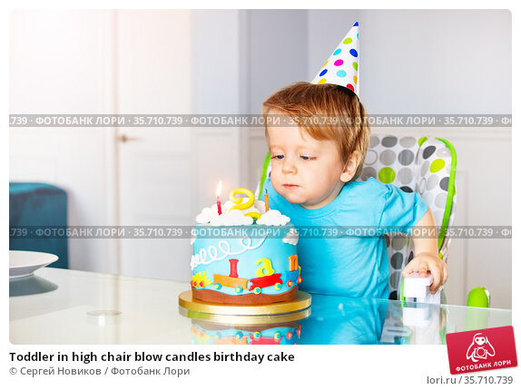 Toddler in high chair blow candles birthday cake. Стоковое фото, фотограф Сергей Новиков / Фотобанк Лори