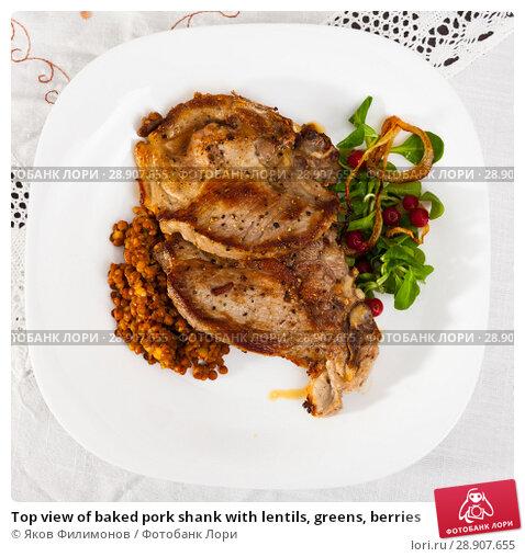 Купить «Top view of baked pork shank with lentils, greens, berries», фото № 28907655, снято 20 марта 2019 г. (c) Яков Филимонов / Фотобанк Лори