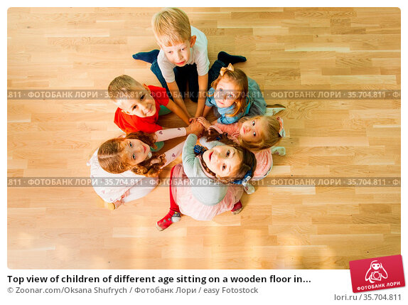Top view of children of different age sitting on a wooden floor in... Стоковое фото, фотограф Zoonar.com/Oksana Shufrych / easy Fotostock / Фотобанк Лори
