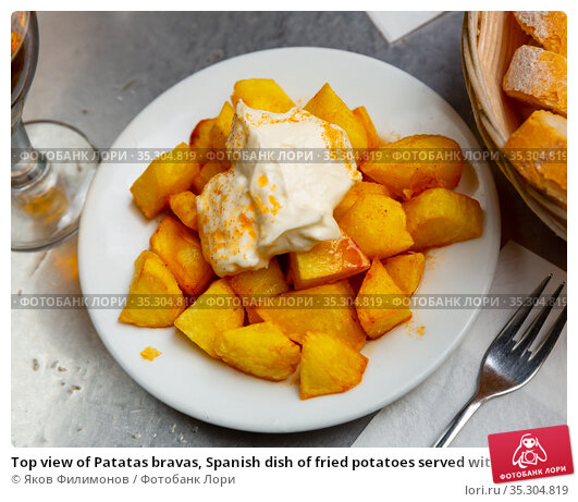 Top view of Patatas bravas, Spanish dish of fried potatoes served with cheese sauce and spicy sauce with paprika. Стоковое фото, фотограф Яков Филимонов / Фотобанк Лори