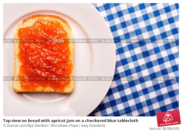 Top view on bread with apricot jam on a checkered blue tablecloth. Стоковое фото, фотограф Zoonar.com/Ilya Starikov / easy Fotostock / Фотобанк Лори