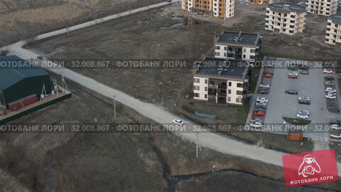 Купить «tracking from the air for a car moving in the residential area», видеоролик № 32008867, снято 5 июня 2019 г. (c) Aleksandr Sulimov / Фотобанк Лори