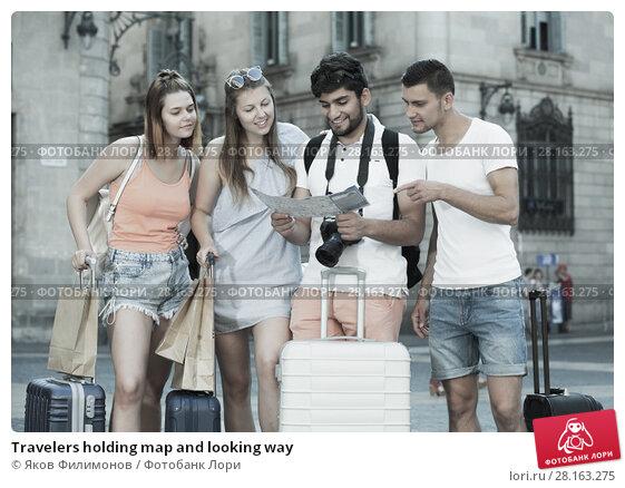 Купить «Travelers holding map and looking way», фото № 28163275, снято 22 июня 2017 г. (c) Яков Филимонов / Фотобанк Лори