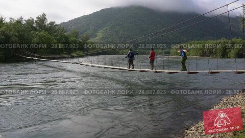 Купить «Туристы переходят реку по подвесному мосту», видеоролик № 28887923, снято 4 августа 2018 г. (c) А. А. Пирагис / Фотобанк Лори