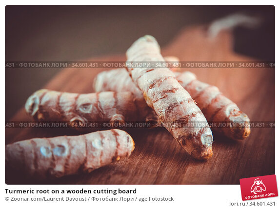 Turmeric root on a wooden cutting board. Стоковое фото, фотограф Zoonar.com/Laurent Davoust / age Fotostock / Фотобанк Лори