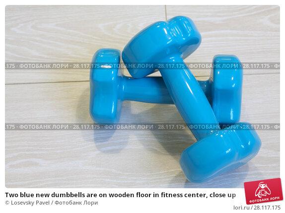 Купить «Two blue new dumbbells are on wooden floor in fitness center, close up», фото № 28117175, снято 22 октября 2016 г. (c) Losevsky Pavel / Фотобанк Лори