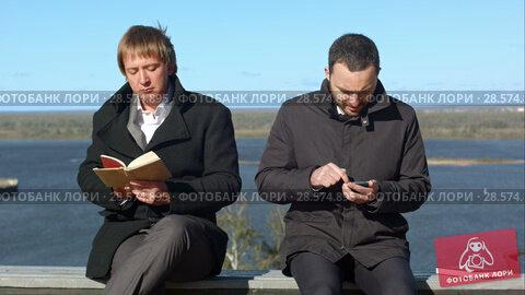Купить «Two business people with phone and book», видеоролик № 28574895, снято 11 октября 2015 г. (c) Vasily Alexandrovich Gronskiy / Фотобанк Лори