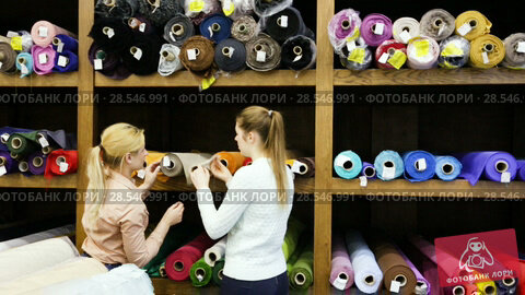 Купить «Two cheerful young female friends looking for interesting cloth in textile shop», видеоролик № 28546991, снято 28 марта 2018 г. (c) Яков Филимонов / Фотобанк Лори