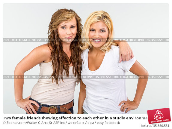 Two female friends showing affection to each other in a studio environment... Стоковое фото, фотограф Zoonar.com/Walter G Arce Sr ASP Inc / easy Fotostock / Фотобанк Лори