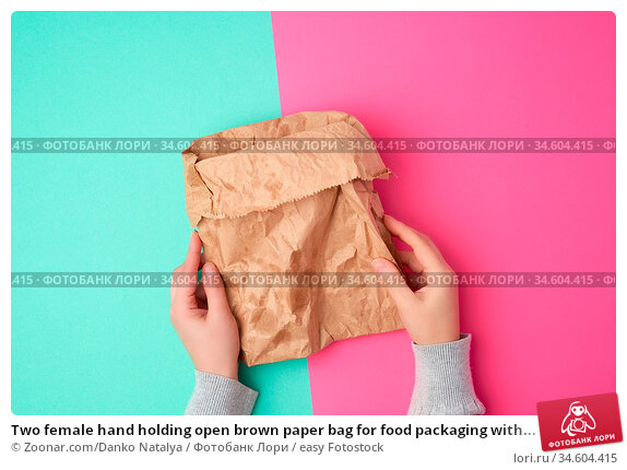 Two female hand holding open brown paper bag for food packaging with... Стоковое фото, фотограф Zoonar.com/Danko Natalya / easy Fotostock / Фотобанк Лори
