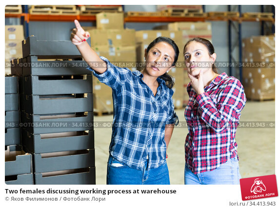 Two females discussing working process at warehouse. Стоковое фото, фотограф Яков Филимонов / Фотобанк Лори