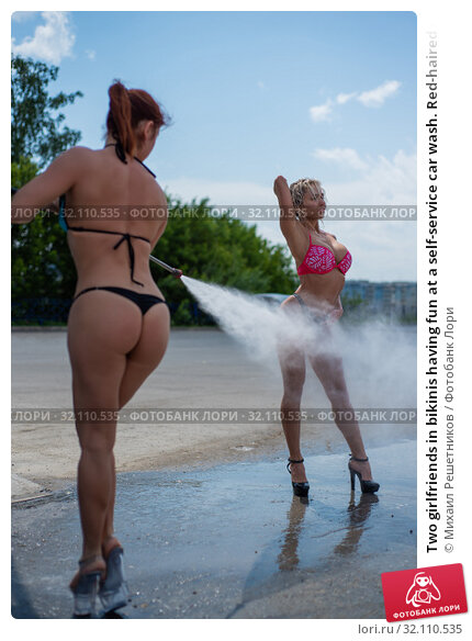Two girlfriends in bikinis having fun at a self-service car wash. Red-haired woman watering a blonde from a gun for a car wash. A beautiful girl sent a jet of high pressure water to her friend. Стоковое фото, фотограф Михаил Решетников / Фотобанк Лори