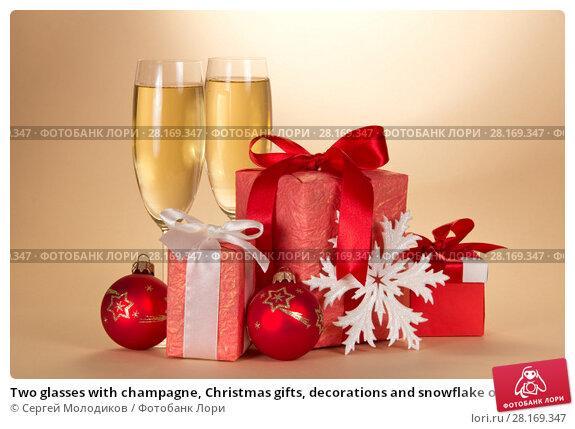 Купить «Two glasses with champagne, Christmas gifts, decorations and snowflake on a beige», фото № 28169347, снято 29 июня 2013 г. (c) Сергей Молодиков / Фотобанк Лори