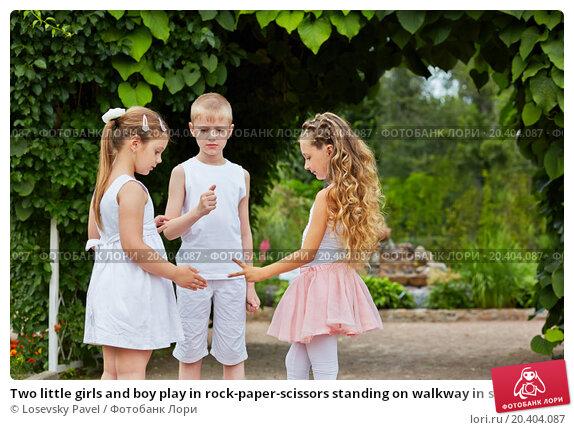 Купить «Two little girls and boy play in rock-paper-scissors standing on walkway in summer park», фото № 20404087, снято 2 июля 2013 г. (c) Losevsky Pavel / Фотобанк Лори