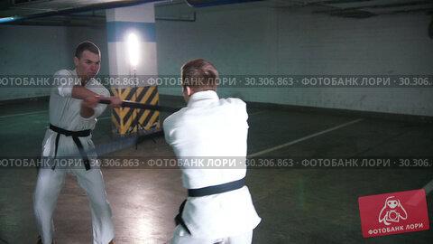 Купить «Two men in kimono training their kendo on a parking lot», видеоролик № 30306863, снято 24 марта 2019 г. (c) Константин Шишкин / Фотобанк Лори