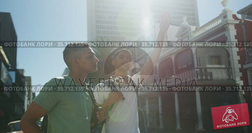 Two mixed race male friends standing, trying to catch cab in the street. Стоковое видео, агентство Wavebreak Media / Фотобанк Лори