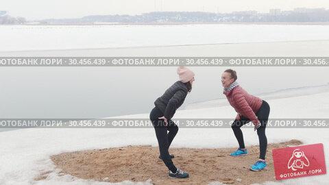 Two slim women standing on the snowy beach and warming up. Стоковое видео, видеограф Константин Шишкин / Фотобанк Лори
