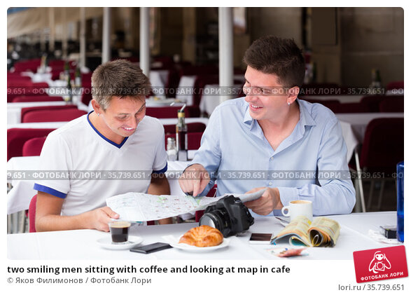 two smiling men sitting with coffee and looking at map in cafe. Стоковое фото, фотограф Яков Филимонов / Фотобанк Лори