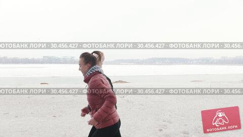 Two smiling women running on a snowy beach. Стоковое видео, видеограф Константин Шишкин / Фотобанк Лори