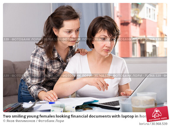 Купить «Two smiling young females looking financial documents with laptop in home interior», фото № 30968539, снято 22 июля 2019 г. (c) Яков Филимонов / Фотобанк Лори
