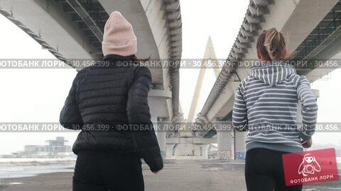 Two women running under the bridge. Стоковое видео, видеограф Константин Шишкин / Фотобанк Лори