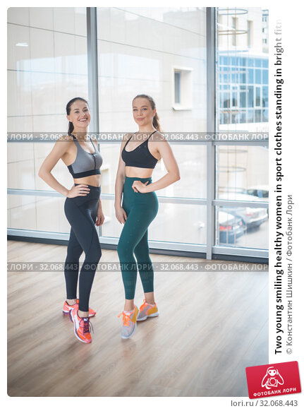 Two young smiling healthy women in sport clothes standing in bright fitness studio. Стоковое фото, фотограф Константин Шишкин / Фотобанк Лори