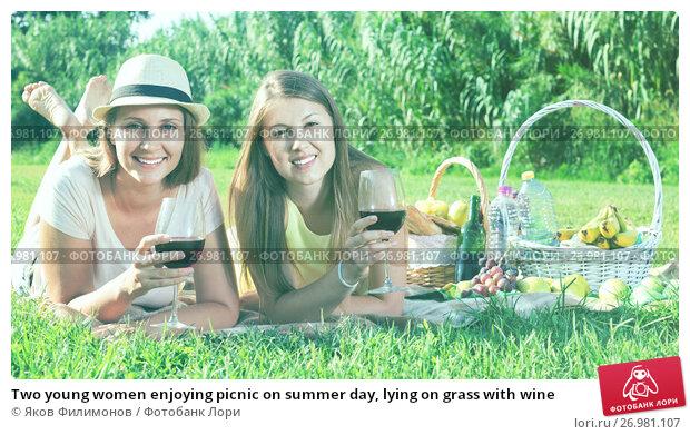 Купить «Two young women enjoying picnic on summer day, lying on grass with wine», фото № 26981107, снято 12 декабря 2017 г. (c) Яков Филимонов / Фотобанк Лори