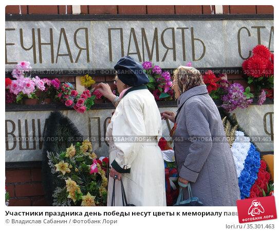 Участники праздника день победы несут цветы к мемориалу павшим воинам (2017 год). Редакционное фото, фотограф Владислав Сабанин / Фотобанк Лори