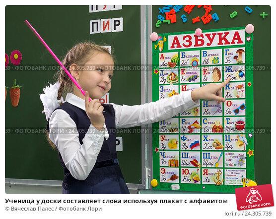 Ученица у доски составляет слова используя плакат с алфавитом (2012 год). Редакционное фото, фотограф Вячеслав Палес / Фотобанк Лори