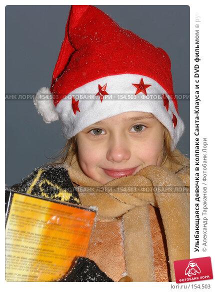 Улыбающаяся девочка в колпаке Санта-Клауса и с DVD фильмом в руках, эксклюзивное фото № 154503, снято 25 марта 2017 г. (c) Александр Тараканов / Фотобанк Лори