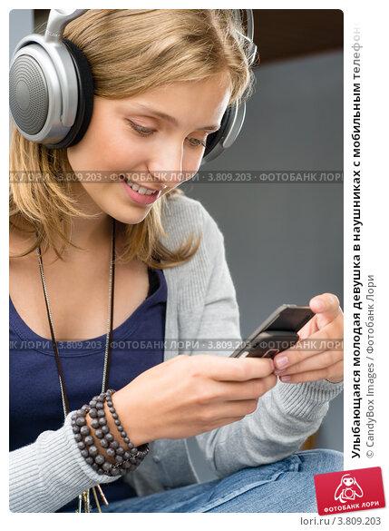 Улыбающаяся молодая девушка в наушниках с мобильным телефоном. Стоковое фото, фотограф CandyBox Images / Фотобанк Лори