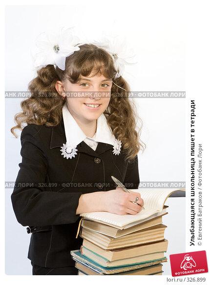 Улыбающаяся школьница пишет в тетради, фото № 326899, снято 23 марта 2008 г. (c) Евгений Батраков / Фотобанк Лори