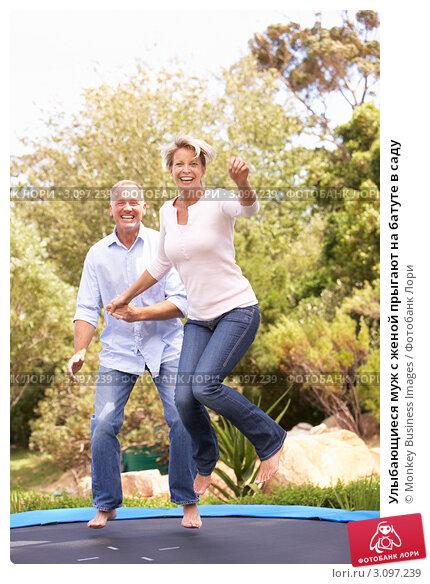 Улыбающиеся муж с женой прыгают на батуте в саду, фото № 3097239, снято 27 февраля 2010 г. (c) Monkey Business Images / Фотобанк Лори