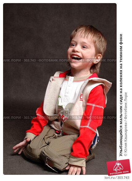 Улыбающийся мальчик сидя на коленях на темном фоне, фото № 303743, снято 23 марта 2008 г. (c) Юлия Кашкарова / Фотобанк Лори