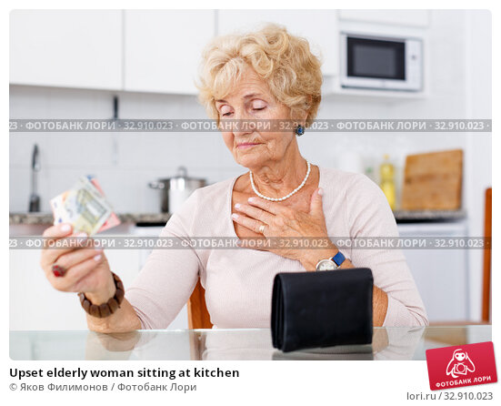 Upset elderly woman sitting at kitchen. Стоковое фото, фотограф Яков Филимонов / Фотобанк Лори